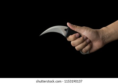 close up of hand holding a karambit knife, isolated on black background with clipping path