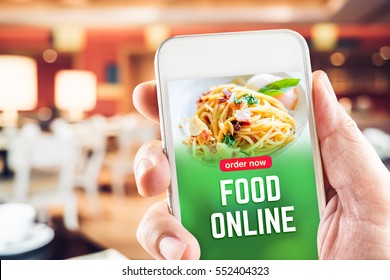 Close up hand holding mobile with order food online word on screen with blur restaurant bokeh light background,online marketing concept.