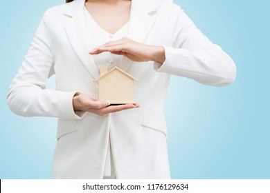 Close up of hand holding model house, Home Buying Ideas Auction Residential Property Service offered by the agent. The monthly installment. isolated  on blue background and clipping path