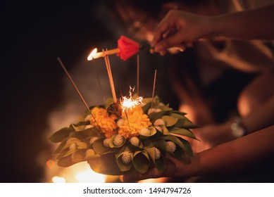 Close up of hand holding natural Kratong with candle and stick to floating on a river at night in Loy Krathong festival, traditional Siamese new year festival celebrated in Thailand.