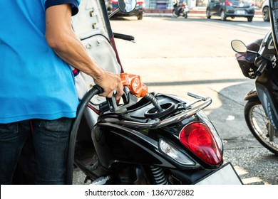 Close up of hand holding nozzle fuel filling oil into motorcycle tank. Transportation and energy concept.