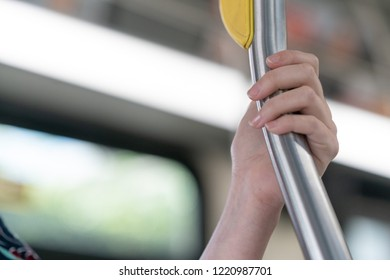 Close up of hand holding on a bar in a bus