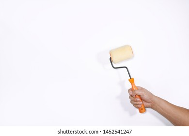 close up hand holding painting roller for colors painting on white background. Painter holding brush for painting house on the isolated background.