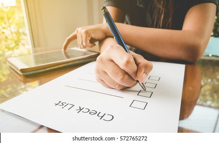 close- up hand holding pen on check list paper with tablet in vintage style