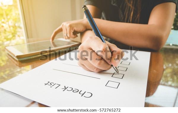 チェックリスト用紙にペンを持つ接写とビンテージスタイルのタブレット