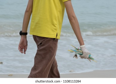 Close Up Of Hand Holding Plastic Straws Polluting Beach.