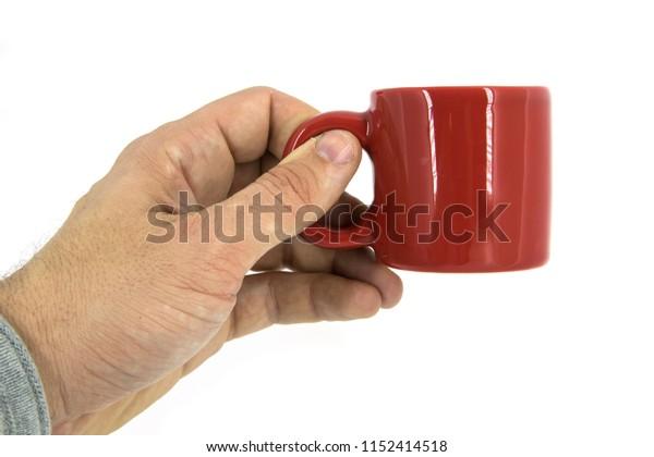 Close up of a hand holding a red mug