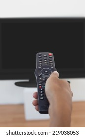 Close up of hand holding remote and changing channel