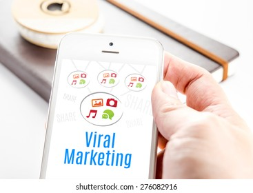 Close up hand holding smart phone with Viral marketing word and icons with notebook at background, Mobile technology concept