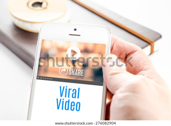 Close up hand holding smart phone with Viral Video word and icons with notebook at background, Mobile technology concept