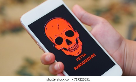 Close up - hand holding a smartphone with an image of Petya ransomware warning appear on its screen