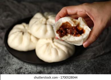 Close up hand holding a steamed pork bun, Chinese dim sum cuisine.