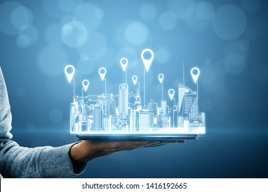 Close up of hand holding tablet with city hologram and location pins on blurry background with bokeh circles. Map and innovation concept