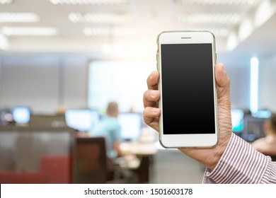 Close up hand holding white smartphone on blank screen at office blur background clipping path inside