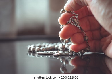 Close up of hand with the holy rosary to pray with light and shadows and reflection on the table in vintage tone. Beautiful Roman Catholicitem, rosary made from silver. Life of faith concept.