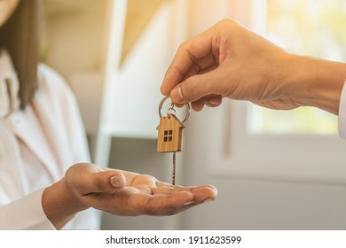 Close up hand of home,apartment agent or realtor was holding the key to the new landlord,tenant or rental.After the banker has approved and signed the purchase agreement successfully.Property concept.