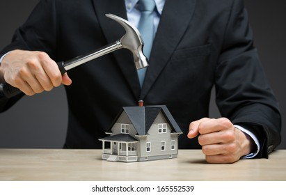 Close up of hand keeping hammer over little house. Concept of real estate and damage