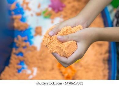 close up hand of kid playing Synthetic sand