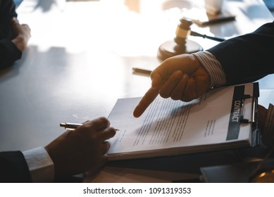 Close up of hand lawyer working and customer signing contract paper with wooden gavel judge in the office. lawyer and law ,judiciary and legislature courtroom legal concept.