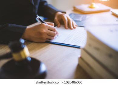 Close up of hand lawyer working for signing important documents with wooden gavel judge in the office. lawyer and law ,judiciary and legislature courtroom legal concept.