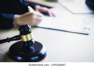 Close up of hand lawyer working signing contract paper with wooden gavel judge in the office. lawyer and law ,judiciary and legislature courtroom legal concept.