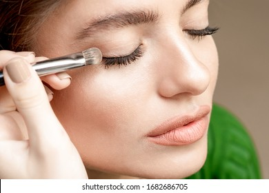 Close up hand of makeup artist applies eyeshadow powder, eyes makeup with copy space.