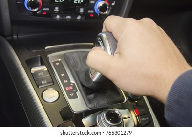Close up of hand of male driver shifting gear stick before driving car