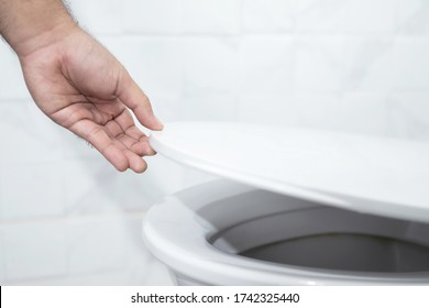 close up hand of a man closing the lid of a toilet seat. Hygiene and health care concept.