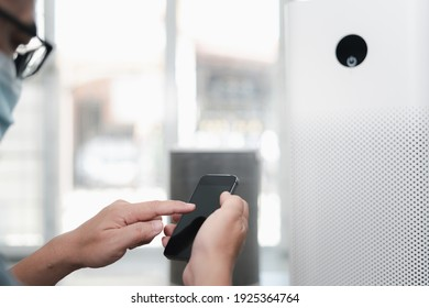 Close up hand a man hold smartphone and use Application for control Air purifier in home network remote device control on internet