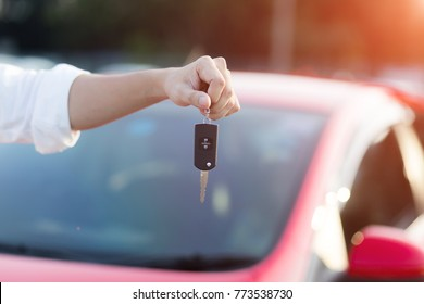Close up hand of Man holding car key  with blurred red car on background.