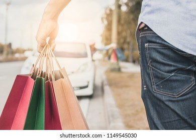 Close up hand of man holding paper bag shopping and walking to car and girl friend waiting.
