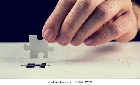 Close up of the hand of a man placing the last piece in place in a jigsaw puzzle conceptual of problem solving, finding a solution and meeting a challenge.