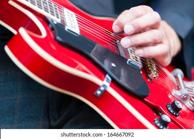 Close up of the hand of a man playing an electric guitar plucking the strings with his fingers during a live performance with a band or orchestra