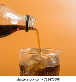 Close up of hand of a man pour cola soda drink into a glass with ice cube in orange background, hot and thirsty concept
