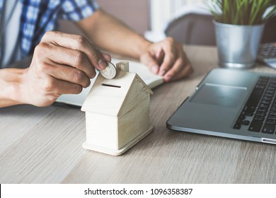 close up hand of man putting on bank saving for investment in property.