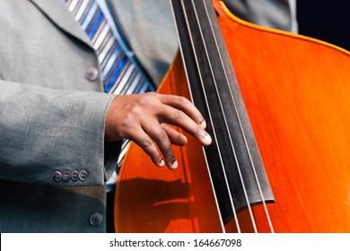 Close up of the hand of a man sitting playing a double bass in an orchestra, a large wooden stringed instrument played with a very low pitch popular in classical, jazz and blues genres of music