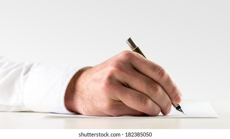 Close up of the hand of a man writing on a sheet of paper with a fountain pen conceptual of handwritten correspondence or of signing an agreement or business contract.