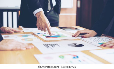 close up hand of marketing manager employee pointing at business document during discussion at meeting room , Notebook on wood table - Business concept