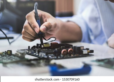 Close up of the hand men hold tool repairs electronics manufacturing Services, Manual Assembly Of Circuit Board Soldering.