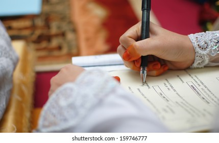 close up hand of a muslimah bride signing on the form of registration for muslim wedding. focusing on the hand with shallow depth of field