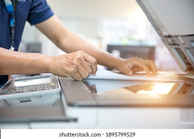 Close up hand of office man is press button on panel and put paper on the copier machine in copy room for scanning document printing a sheet and xerox photocopy.