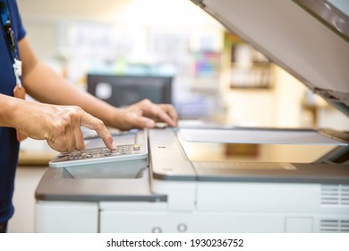 Close up hand of office man press the copy button on panel to using the copier or photocopier machine in copy room for scanning document printing a sheet and xerox photocopy.