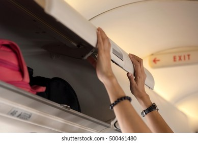 close up of hand open overhead locker on airplane