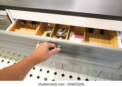 Close up of hand opening a grey drawer in the kitchen