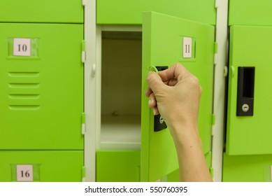 Close up hand opening the locker door.