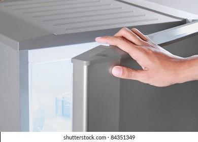 close up of hand opening refrigerator