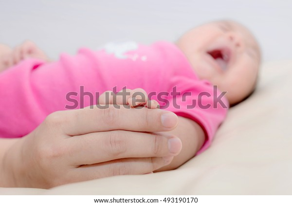 Close up hand of parent clasping hand and fingers infant..