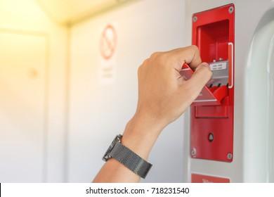 Close up hand of passenger pulling  handle of emergency egress train door for open train door in evacuation situation