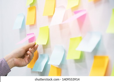 close up hand people business man  notes pad in the wall at meeting room. Sticky post note paper reminder schedule board. Colorful variety copy empty space. soft focus.