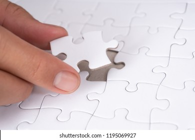 Close up of hand placing the last jigsaw puzzle piece, Hand holding missing jigsaw puzzle piece down in to the place, conceptual of problem solving.